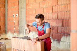 construction-worker-builing-brick-walls-P6GPFRX